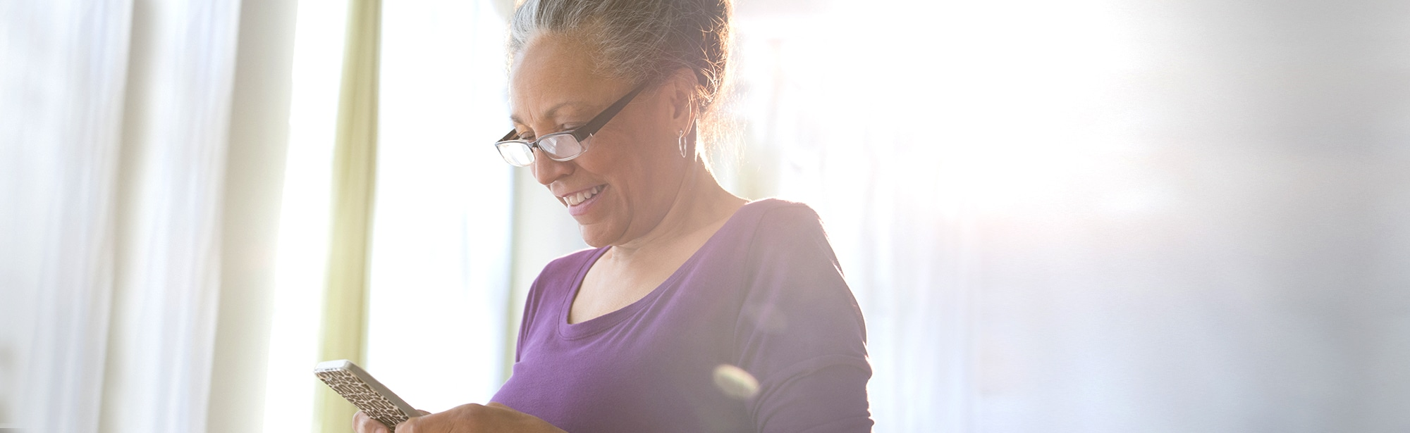 Woman reading smartphone screen smiling
